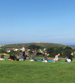 Yoga lesson with sea view of Gull Rocks at Holywell Bay