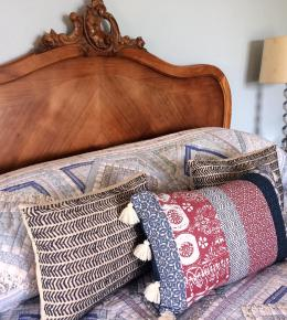 cosy french bed dressed wtih autumnal cushions and quilt