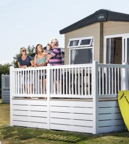 A family standing on the balcony of a static caravan