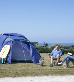 A couple sat on chairs outside there tent in a field on a sunny day