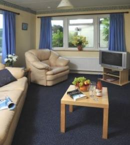 An inviting chalet lounge, with a 2 piece lounge suite and countryside view from the windows