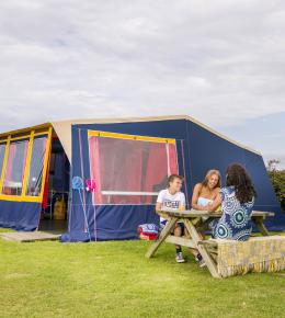 Family sat outside a Ready Tent at Trevornick Holiday Park