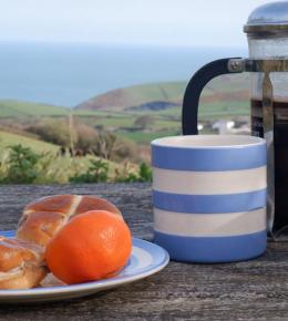 Coffee and buns in Polrunny Farm's breakfast garden, with a sea view