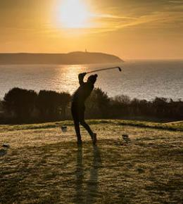 Golfer with sunrise in background