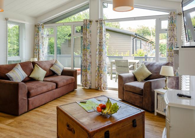 luxury lodge lounge with large windows and comfy sofa. Million Cove