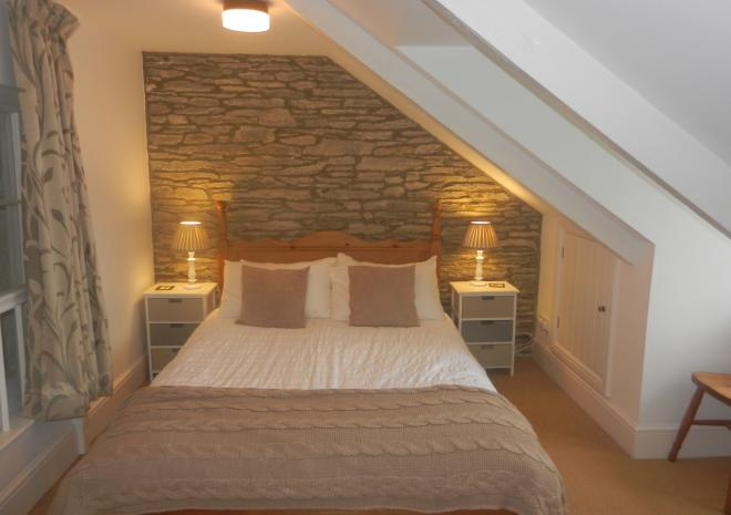 Upstairs double bedroom with en-suite shower room and a view of the sea across the fields.