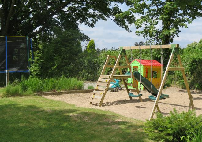 Small childrens play area with swings and slide.Trampoline and wendy house in season