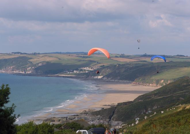 Para gliding off Whitsand Bay cliffs