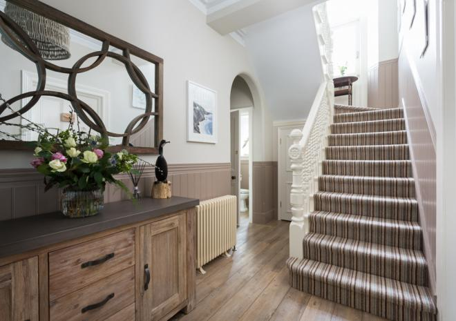 The entrance hall and stairs of Kinbrae House are kept meticulously clean and are adorned with gorgeous artwork and flowers for guests to enjoy.