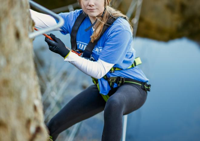 Lady taking on the high wire adventure at Via Ferrata Cornwall