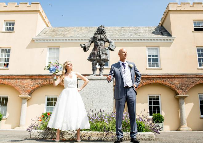 Bride & groom stood at the front of Pentillie Castle with statue of Sir Jimmy Tillie