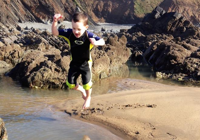 Boy in wetsuit jumping in to sea