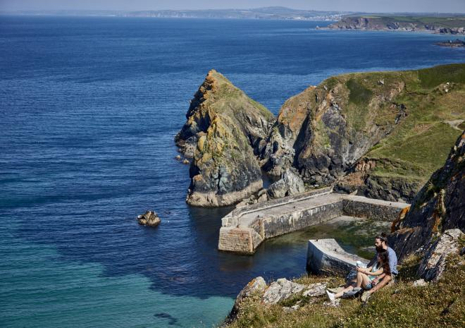 Mullion harbour as seen from the cliffs. The sea is royal blue and a couple enjoy a picnic