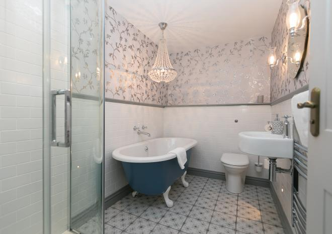 Freestanding bath with chandelier in one of the bathrooms in holiday cottage, Morwenna, at Polmanter Touring Park, St Ives