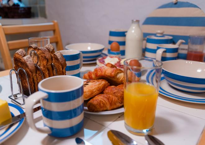 The breakfast table at Blackberry Cottage, Polrunny Farm, complete with vintage blue and white Cornishware crockery.
