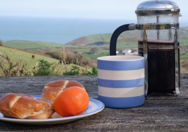 Hot cross buns and coffee on a table at Polrunny Farm, with sea view in the background