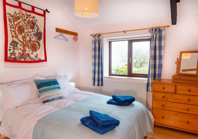 The double bedroom at Seaberry Cottage, Polrunny Farm, with beautiful views through the window of countryside sloping down to the sea