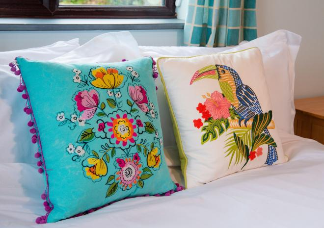 Brightly coloured cushions on the bed at Sloe Cottage, Polrunny Farm