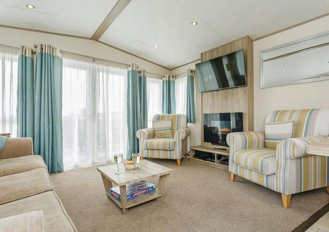 Caravan lounge with stripy armchairs, TV, modern fireplace and patio doors