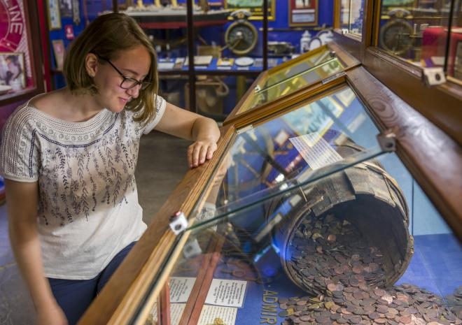 Visitor viewing the world's only ever recovered barrel of coins at Shipwreck Treasure Museum