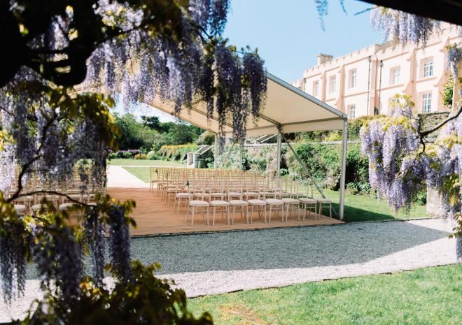 An outdoor ceremony under the wisteria clad pavilion at Pentillie Castle
