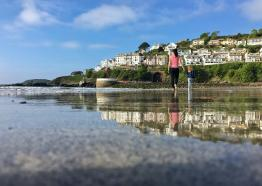 Mother and daughter walking along beach towards Looe